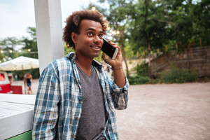 Cheerful african young man talking on cell phone outdoors