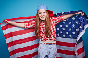 Cheerful American girl with stars-and-stripes looking at camera
