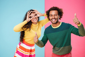 Cheerful amusing african young couple having fun together over colorful background