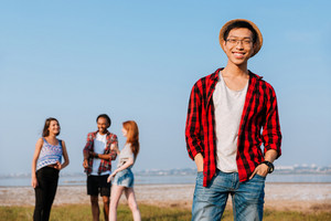 Cheerful asian young man standing while his friends talking outdoors