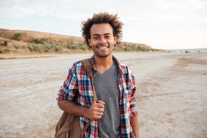 Cheerful attractive african young man standing outdoors and holding backpack