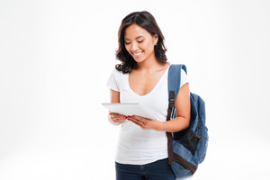 Cheerful attractive asian girl with backpack using tablet computer isolated on a white background
