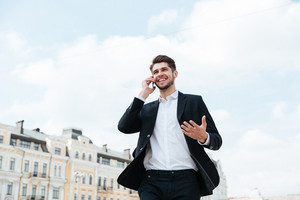 Cheerful attractive young businessman standing on the street and talking on cell phone
