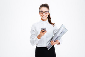 Cheerful attractive young businesswoman in glasses holding folders and using cell phone over white background