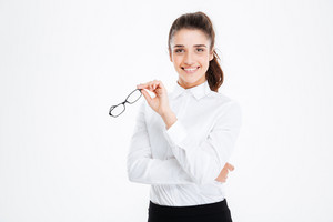 Cheerful attractive young businesswoman standing and holding glasses
