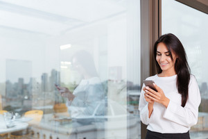 Cheerful attractive young businesswoman standing and using mobile phone near the window