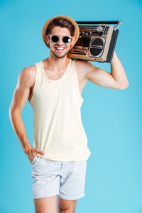Cheerful attractive young man in hat and sunglasses standing and holding boombox over blue background