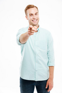 Cheerful attractive young man smiling and pointing at camera over white background