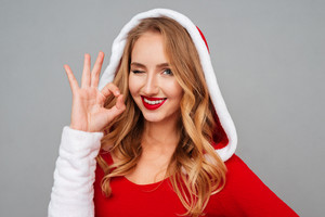 Cheerful attractive young woman in santa costume showing ok sign and winking over grey background