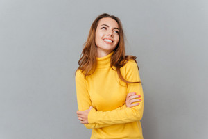 Cheerful attractive young woman in yellow sweater standing with arms crossed and looking away at copy space over gray backgorund