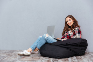 Cheerful attractive young woman sitting and using laptop on black bean bag