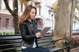 Cheerful attractive young woman sitting and using tablet on the bench in park