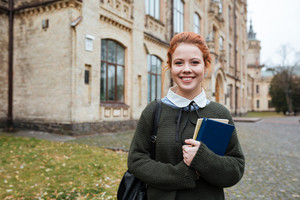 Cheerful attractive young woman student with backpack and books standing in campus