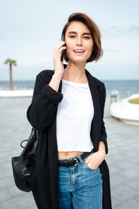 Cheerful attractive young woman walking and talking on cell phone outdoors