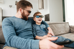Cheerful bearded young father holding remote control while watching TV with his little cute son using 3d glasses.
