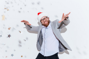 Cheerful bearded young man in glasses and santa claus hat smiling and dancing over white background