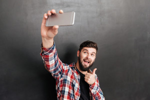 Cheerful bearded young man showing thumbs up and taking selfie with cell phone over grey background