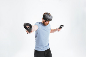 Cheerful bearded young man wearing virtual reality device standing over white background while holding joysticks in hands.