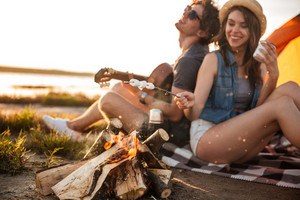 Cheerful beautiful young couple playing guitar and frying marshmallows on bonfire