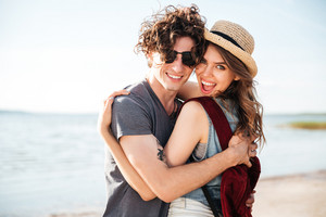 Cheerful beautiful young couple standing and embracing on the beach