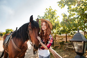 Cheerful beautiful young woman cowgirl standing with her horse in village