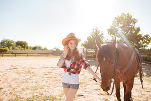 Cheerful beautiful young woman cowgirl walking with her horse on ranch
