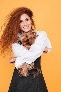 Cheerful beautiful young woman holding and hugging cute dog
