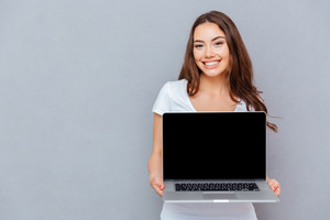 Cheerful beautiful young woman holding blank screen laptop