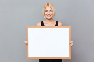 Cheerful beautiful young woman holding blank white board over gray background