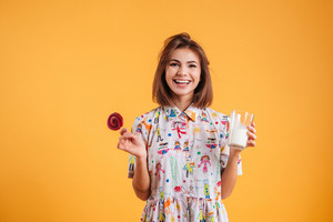 Cheerful beautiful young woman holding glass of milk and sweet lollipop