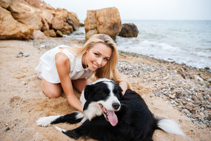 Cheerful beautiful young woman hugging her dog on the beach