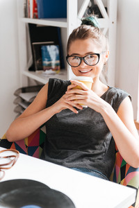 Cheerful beautiful young woman in glasses drinking coffee and relaxing at the table at home