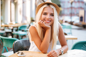 Cheerful beautiful young woman in hat sitting in outdoor cafe