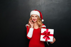 Cheerful beautiful young woman in santa claus costume holding gift box