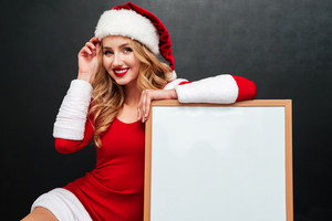 Cheerful beautiful young woman in santa claus costume with blank white board