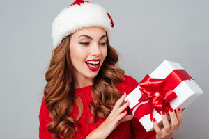 Cheerful beautiful young woman in santa claus hat holding present box over gray background