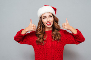 Cheerful beautiful young woman in santa claus hat showing thumbs up over gray background