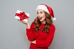 Cheerful beautiful young woman in santa claus holding gift box over gray background