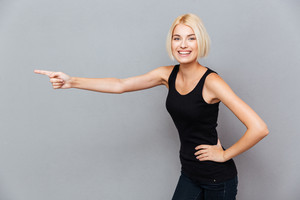 Cheerful beautiful young woman pointing away over gray background