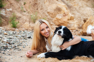 Cheerful beautiful young woman resting and hugging her dog on the beach