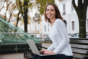 Cheerful beautiful young woman sitting and using laptop on bench in park