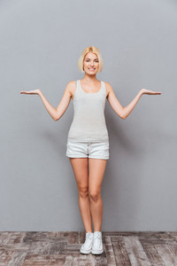 Cheerful beautiful young woman standing and holding copyspace on both palms over gray background