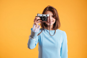 Cheerful beautiful young woman standing and taking photos with old vintage camera over yellow background