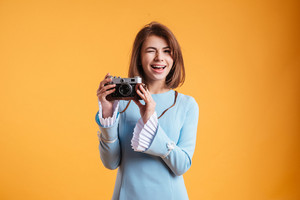Cheerful beautiful young woman winking and using old vintage camera over yellow background