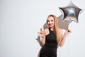Cheerful beautiful young woman with star shaped balloon smiling and drinking champagne over white background