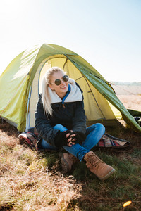 Cheerful blonde woman in sunglasses and boots sitting near tent at campsite outdoors