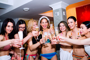 Cheerful bride and happy bridesmaids in bikinis celebrating hen party with champagne. Women enjoying a bachelorette party.