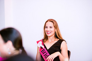 Cheerful bride with pink sash celebrating hen party with bridesmaids. Women enjoying a bachelorette party.