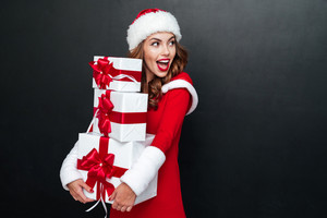 Cheerful brunette woman in red santa claus outfit holding xmas presents isolated on the black background