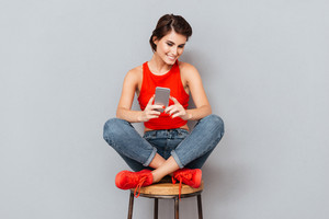 Cheerful brunette woman sitting on the chair and using smartphone over gray background